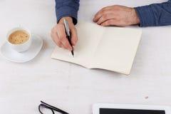 Mężczyzna pisze w notatniku przy białym stołem Fotografia Royalty Free