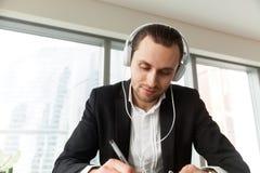 Mężczyzna pisze z piórem przy pracy biurkiem w hełmofonach zdjęcie stock