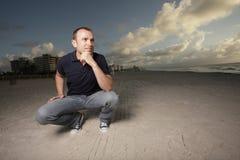 mężczyzna plażowy kucanie zdjęcie stock