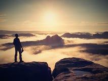 Mężczyzna pobyt z czerwoną nakrętką na skalistym szczycie Mężczyzna chodzi nad skalistym szczytem fotografia stock