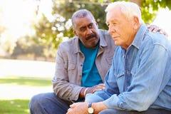 Mężczyzna Pociesza Nieszczęśliwego Starszego przyjaciela Outdoors fotografia royalty free