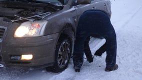 Mężczyzna podnosi samochodowej dźwigarki na drodze mężczyzna zmienia koło samochód zastępstwo toczy wewnątrz zimę na drodze w mie zdjęcie wideo