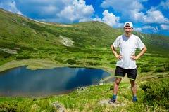Mężczyzna podróżnik na górze gór zbliża jezioro Obrazy Royalty Free