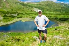 Mężczyzna podróżnik na górze gór zbliża jezioro Obrazy Stock