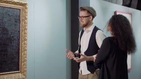 Mężczyzna podziwia współczesną grafikę w galerii, opowiada z kobietą zbiory