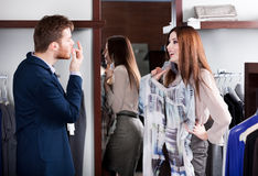 Mężczyzna pokazuje że smokingowi kostiumy jego dziewczyna Zdjęcia Royalty Free