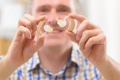 Mężczyzna pokazuje głuche pomoce Obraz Royalty Free