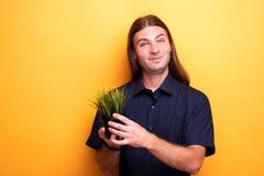 Mężczyzna pokazuje mieszkanie rośliny w garnku zdjęcie royalty free