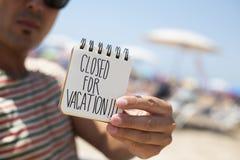 Mężczyzna pokazuje notatkę z tekstem zamykającym dla wakacje Zdjęcie Royalty Free