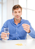 Mężczyzna pokazuje udział pigułki w domu zdjęcia stock