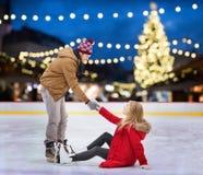 Mężczyzna pomaga kobieta na bożego narodzenia łyżwiarskim lodowisku Zdjęcie Stock