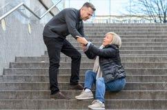 Mężczyzna pomaga kobieta wstawał Obrazy Stock