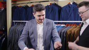 Mężczyzna pomaga próbować dalej kostium w sklepie odzieżowym inny zbiory