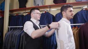 Mężczyzna pomaga próbować dalej kostium w sklepie odzieżowym inny zbiory wideo