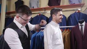 Mężczyzna pomaga próbować dalej kostium w sklepie odzieżowym inny zdjęcie wideo