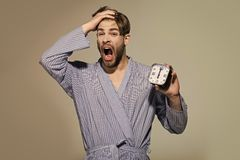 Mężczyzna poziewanie z budzikiem na popielatym tle zdjęcia royalty free