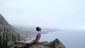 Mężczyzna pozycja na krawędzi falezy w pozie pies z widokami ocean, oddycha w dennym powietrzu podczas a zdjęcie wideo