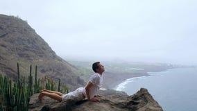 Mężczyzna pozycja na krawędzi falezy w pozie pies z widokami ocean, oddycha w dennym powietrzu podczas a zbiory wideo