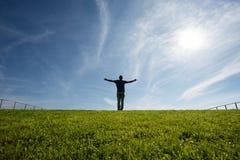 Mężczyzna pozycja na trawie w świetle słonecznym Zdjęcie Stock