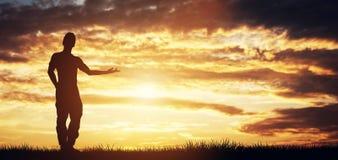 Mężczyzna pozycja na zmierzchu niebie wskazuje dobrze Fotografia Royalty Free