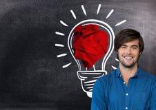 Mężczyzna pozycja obok żarówki z zmiętą papierową piłką przed blackboard Fotografia Royalty Free