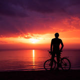 Mężczyzna pozycja z rowerem przy zmierzchem morzem obraz stock