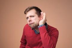 Mężczyzna próbuje słuchać opóźniona plotka w czerwonym pulowerze fotografia royalty free