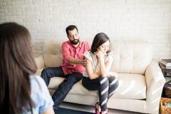 Mężczyzna próbuje uzupełniał konflikt z żoną podczas terapii zdjęcia stock
