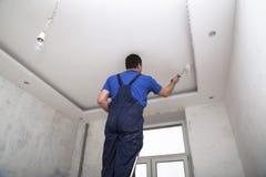 Mężczyzna pracownik maluje ceilin wśrodku izbowego wnętrza Obrazy Royalty Free