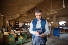 Mężczyzna pracownik w ciesielka warsztacie, robi planom obrazy royalty free