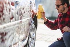 Mężczyzna pracownika ` s płuczkowy samochodowy aliaż toczy na samochodowym obmyciu zdjęcia stock