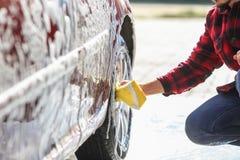 Mężczyzna pracownika ` s płuczkowy samochodowy aliaż toczy na samochodowym obmyciu zdjęcie royalty free