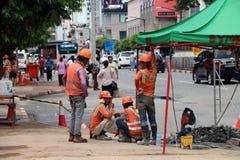 Mężczyzna pracuje budowę z pomarańczowym kolorem zbawczy hełm i zbawcza kamizelka na miasta tle obrazy royalty free