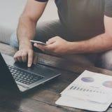 Mężczyzna pracuje laptop i smartphone na kanapie w domu Obraz Stock