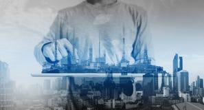 Mężczyzna pracuje na cyfrowej pastylce z elektrownią, rafineria ropy naftowej przemysłu budynków fabryczny hologram zdjęcie royalty free