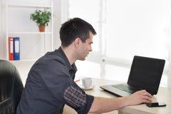 Mężczyzna pracuje na laptopie w biurze obraz royalty free
