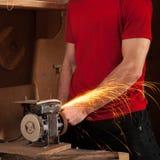 Mężczyzna pracuje na szlifierskiej maszynie bez zbawczego wyposażenia, iskry lata, Zdjęcie Stock