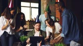 Mężczyzna pracuje w biurze, on dmucha gdy jego koledzy przynoszą on tortowy i gratulują on na urodziny