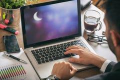 Mężczyzna pracuje w biurze Półksiężyc księżyc na ekranie komputerowym, zdjęcie royalty free
