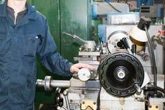 Mężczyzna pracuje w kontuszu, kombinezonów stojaki obok przemysłowej tokarki dla ciąć, obraca noże od metali, drewno inni materia fotografia stock