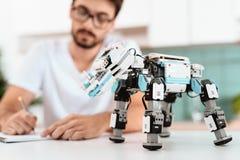 Mężczyzna programuje robot w kuchni W pobliżu jest i szary laptop robot Obrazy Royalty Free