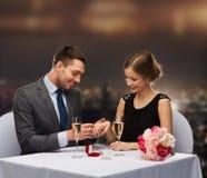 Mężczyzna proponuje jego dziewczyna przy restauracją Zdjęcia Stock