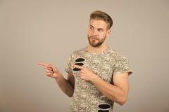 Mężczyzna przedstawia produkt na popielatym tle Macho z brodatym twarz punktu palca gestem Prezentacja, ogłoszenie obrazy stock