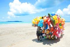 Mężczyzna przejażdżki wiszącej ozdoby sklepu sprzedawanie bawi się dziecko na plaży w Wschodnim Tajlandia Zdjęcia Royalty Free
