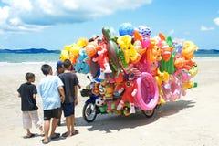 Mężczyzna przejażdżki wiszącej ozdoby sklepu sprzedawanie bawi się dziecko na plaży w Wschodnim Tajlandia Obraz Stock
