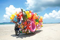 Mężczyzna przejażdżki wiszącej ozdoby sklepu sprzedawanie bawi się dziecko na plaży w Wschodnim Tajlandia Zdjęcie Royalty Free
