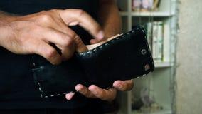 Mężczyzna przelicza pieniądze w portflu ręki mężczyzna zakończenie up zbiory wideo