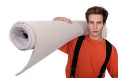 Mężczyzna przewożenia dywan obraz stock