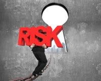 Mężczyzna przewożenia ryzyka czerwony słowo na łańcuchu w kierunku keyhole pejzażu miejskiego Fotografia Royalty Free