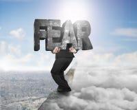 Mężczyzna przewożenia strachu betonu słowo na grani z cloudscape citysca Zdjęcia Stock
